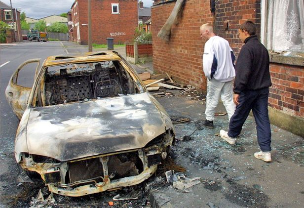 A burnt-out car after three nights of rioting