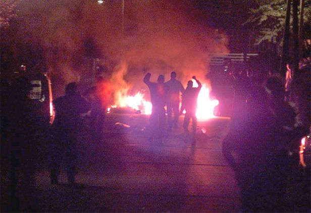 Protesters taunt police officers near a burning road block on the streets of Oldham in May 2001